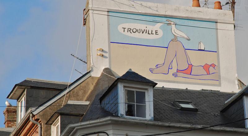 Peinture murale sur une façade d'un immeuble à Trouville. Cette peinture murale représente une mouette annonçant le nom de la ville.