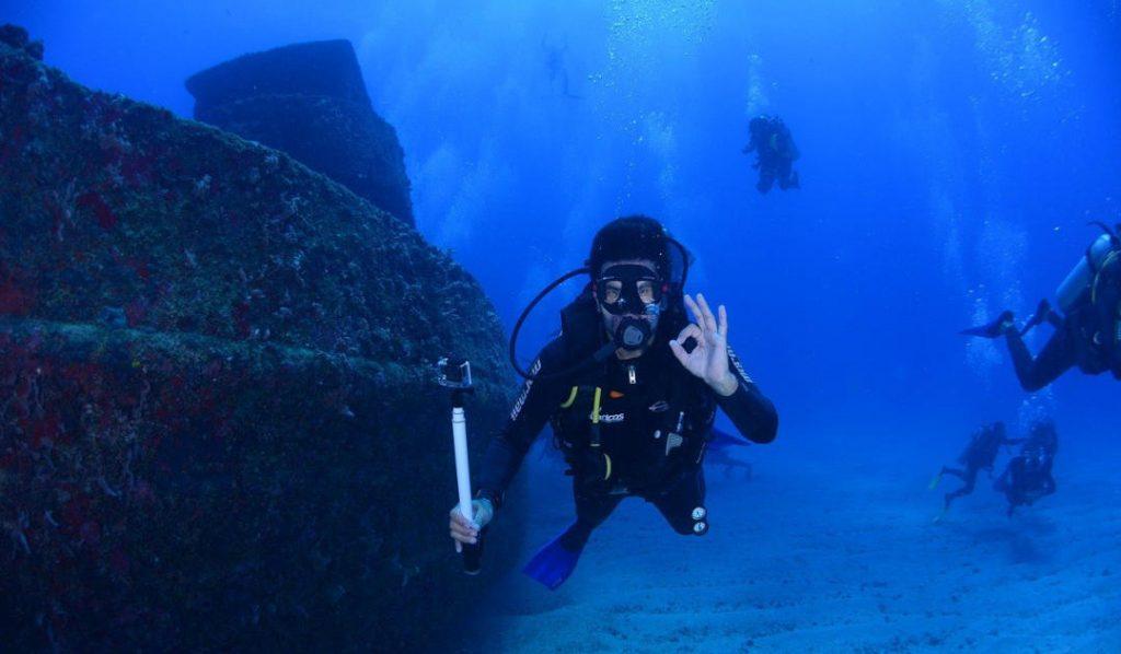 Plongeur devant une épave indiquant que tout va bien.